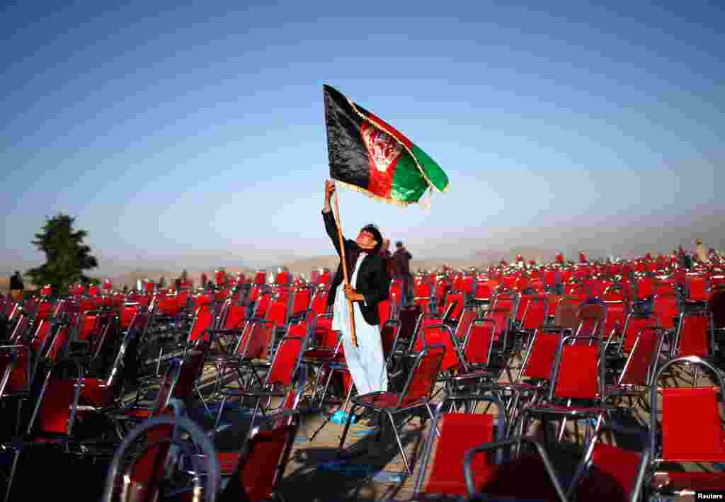 A supporter of Afghan presidential candidate Abdullah Abdullah holds aloft the country's flag after an election campaign rally in the Paghman district of Kabul. (Reuters/Ahmad Masood)