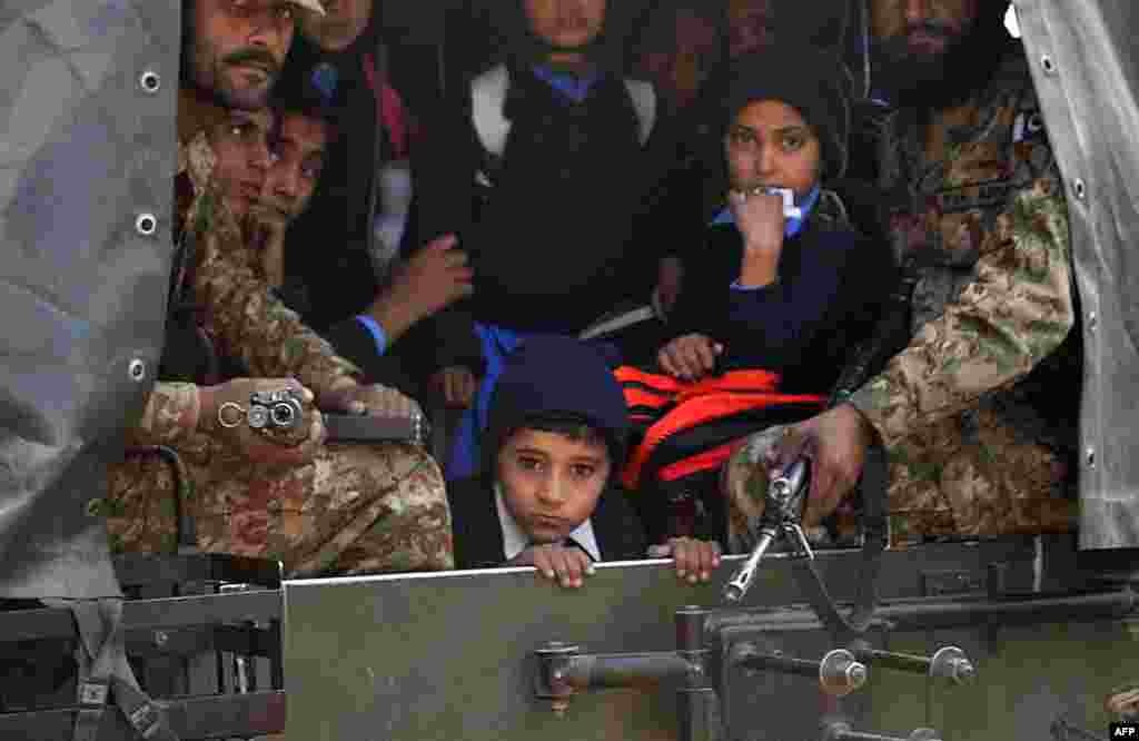 Pakistani soldiers transport rescued schoolchildren from the site of the attack.