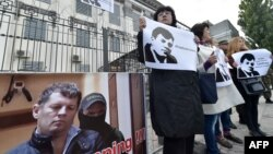 Ukrainian journalists hold placards depicting their colleague Roman Sushchenko during a protest to call for his in front of the Russian Embassy in Kyiv on October 6.