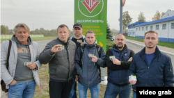 Workers from the Belorusneft petroleum company who were fired after supporting the national strike show their ID cards.