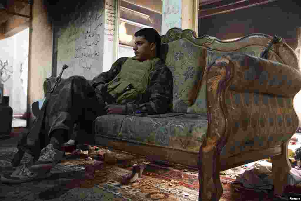 A Free Syrian Army fighter rests on a sofa inside a house in Deir al-Zor. (Reuters/Khalil Ashawi)