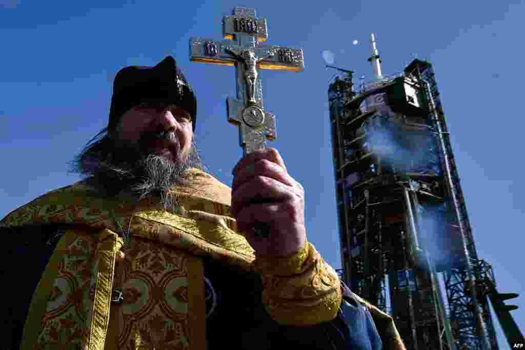 A Russian Orthodox priest conducts a blessing in front of the Soyuz TMA-20M spacecraft at the launch pad of the Russian-leased Baikonur Cosmodrome in Kazakhstan on March 17. (AFP/Kirill Kudryavstev)