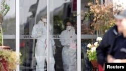Medical personnel leave a quarantined hotel in Skopje, Macedonia, after a man was taken to hospital with symptoms associated with the Ebola virus.