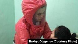 Бакыт Утаганов осматривает пациентку инфекционной больницы в Алматы.