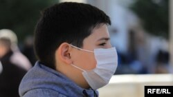 A child in Pristina wears a mask to protect against coronavirus.