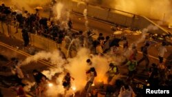 Полицейские распыляют слезоточивый газ для разгона демонстрации. Гонконг, 29 сентября 2014 года.