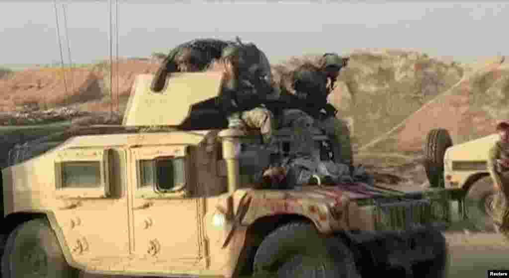A Humvee with the body of a dead Taliban fighter on its hood on July 7 after fighting around the northern city of Kunduz.