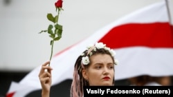 Жінка тримає квітку під час демонстрації опозиції на знак протесту проти результатів президентських виборів. Мінськ, 22 серпня 2020 року