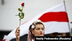 Девушка держит цветок во время демонстрации в знак протеста против результатов президентских выборов. Минск, 22 августа 2020 года.