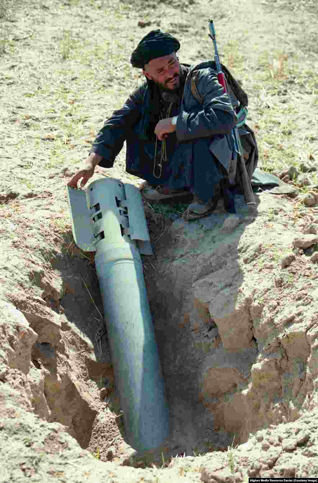 "A mujahedin fighter with an unexploded Soviet rocket. When the AMRC archive was handed to the U.S. Library of Congress in 2016, a speaker noted the images filled ""a huge gap"" in the visual record of the Soviet Union's last war."