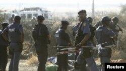 ОАР полициясы оқ тиіп, қаза тапқан адамдардың мәйітіне қарап тұр. 16 тамыз 2012 жыл.