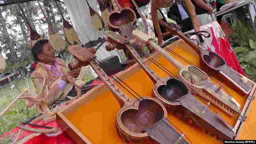 «Мәңгілік ел» фестивалінде қазақ ұлттық музыка аспаптары жәрмеңкесі өтті. Сөреге қобыз, домбыра қойылған.