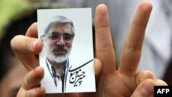 Іран - Прихильник кандидата у президенти Міра Хосейна Мусаві, тримає його зображення під час передвиборного мітингу на стадіоні у Тегерані, 9 червня 2009 р.