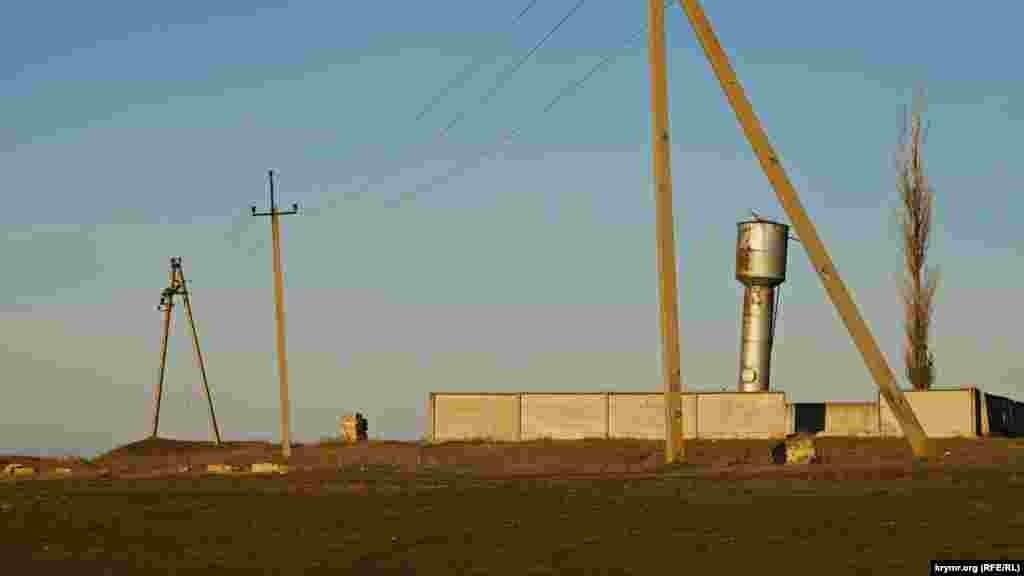 Одна из двух водонапорных башен возле геотермальной скважины заметно покосилась.