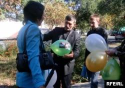 Активисты партии «Азат» раздают прохожим шары с фотографией осужденного правозащитника Евгения Жовтиса. Талдыкорган, 6 октября 2009 года.