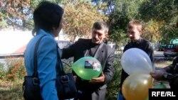 Активисты «Азата» раздают прохожим шары с фотографией осужденного правозащитника Евгения Жовтиса. Талдыкорган, 6 октября 2009 года.