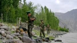 Tajik border guards patrolling the Tajik-Afghan border on the Panj River outside the city of Panj