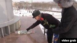 Астанадағы «Атамекен» этномемориалдық кешеніндегі мемлекеттік ту түбіне гүл шоқтарын қойып жатқан белсенділер. 16 желтоқсан 2015 жыл.