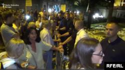 """Učesnici protesta """"1 od 5 miliona"""" sa leve i pripadnici vojnog obezbeđenja (u civilu) sa desne strane zaštitne ograde tokom protesta u subotu 10. avgusta"""