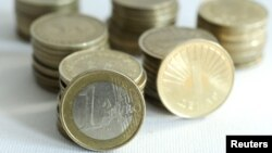 Macedonia -- An one euro coin is balanced against stacks of Macedonian one denar coins, 25Jan2011