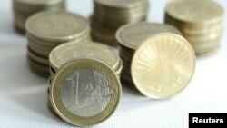 Macedonia -- An one euro coin is balanced against stacks of Macedonian one denar coins, 25Jan2011