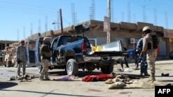 عناصر أمن يتفحصون آثار عملية نفذها عناصر القاعدة في مدينة حديثة