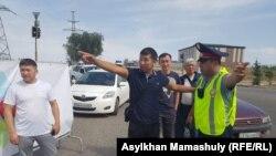 Водители жалуются дорожному полицейскому на заторы из-за перекрытых улиц. Алматы, 18 августа 2018 года.