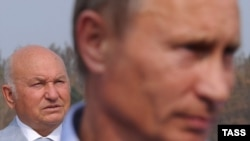 Moscow Mayor Yury Luzhkov (left) looks on as Russian Prime Minister Vladimir Putin faces the media in August.