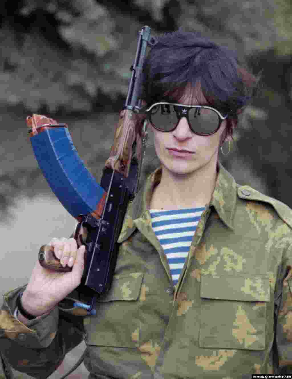 "A female Ossetian fighter poses for a portrait.   A Russian woman married to a Georgian told Human Rights Watch she attempted to find help after the couple's house was robbed but was told ""you [cooked] this porridge, now eat it!"""
