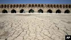 In this Tuesday, July 10, 2018 photo, the Zayandeh Roud river no longer runs under the 400-year-old Si-o-seh Pol bridge, named for its 33 arches, in Isfahan, Iran. Farmers in central Iran are increasingly turning to protests, pleading to authorities for a