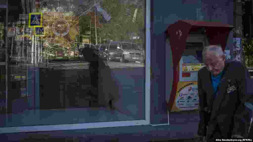 Ветеран проходить повз магазин, вітрина якого прикрашена святковою символікою, недалеко від парку Треньова в Сімферополі