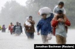 Местные жители покидают дома из-за наводнения, вызванного ураганом «Харви». Бтюмонт Плейс, 28 августа 2017 года.