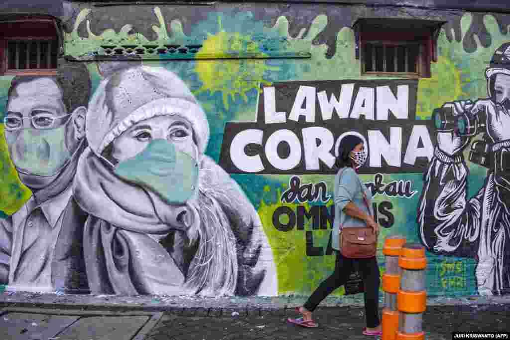 Индонезийка минава пред графит, който призовава за борба срещу коронавируса в Сурабая, провинция Източна Ява.