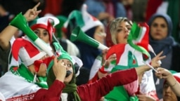 Iranian women cheer during the World Cup Qatar 2022 Group C qualification football match between Iran and Cambodia at the Azadi stadium in the capital Tehran on October 10, 2019.