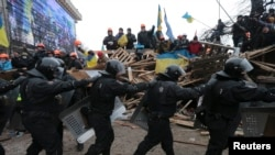 A line of riot police marches past pro-European integration protesters manning barricades on Independence Square in Kyiv on December 11.