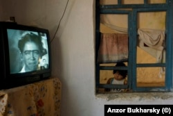 A girl watches a Soviet-era film in a Romany village near Bukhara. The village is one of Anzor's favorite places to photograph after he was accepted into the community several years ago.