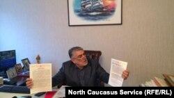 Магомедпазил Махачев показывает документы на участок у озера Ак-Гель