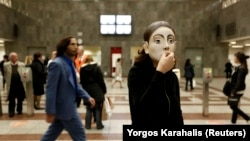 An actor performs at central Syntagma metro station in Athens