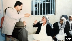 Saddam Hussein (left) drinks tea with elders in Mosul in 1993.