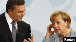 German Chancellor Angela Merkel (right), seen at a 2010 meeting with Ukrainian President Viktor Yanukovych, has threatened to stay away from Ukraine during Euro 2012.