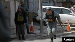 Afghan police officers take up positions during the attacks in Kabul on April 15.