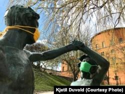 Скульптуры в защитных масках около центральной библиотеки Стокгольма