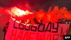 """Sprijinitori ai opoziției ruse cu un banner pep care scrie: """"Eliberați-o pe Nadejda Savcenko, eliberați deținuții politici!"""", Moscova, 26 ianuarie 2015."""