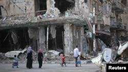 Люди идут вдоль разрушенных войной домов. Сирия, 4 сентября 2013 года.