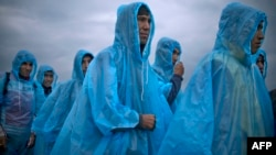 Migrants and refugees wearing raincoats queue at a camp to register after crossing the Greek-Macedonian border near Gevgelija, Macedonia.