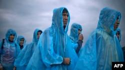 Migranți și refugiați, așteptând să se înregistreze într-o tabără din Macedonia, după ce au trecut frontiera greacă, 22 septembrie 2015