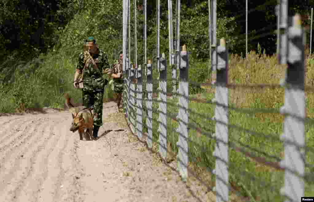 Border guards walk with a dog near the Belarus-Poland border on the outskirts of the western city of Brest, 21Jun2013