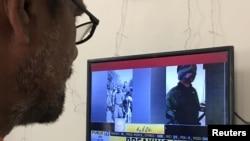 مردی روز چهارشنبه در حال تماشای تصاویری که گفته می شود خلبان هندی به اسارت گرفته شده درپاکستان است.