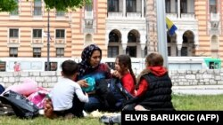 A migrant woman with children rests in the park across from city hall in Sarajevo.