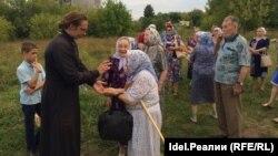 Отец Роман с прихожанами на месте, где будет заложен каменный фундамент храма Ксении Петербургской